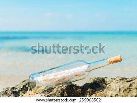 Bottle with message on the beach. Space for your text. - stock photo