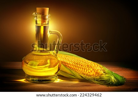 Bottle with oil and a corncob. - stock photo