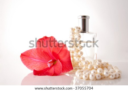 Bottle with perfume, a pearl necklace and a red flower - stock photo