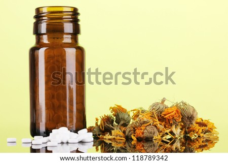 bottle with pills and herbs on green background. concept of homeopathy - stock photo