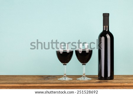 Bottle with red wine and glasses on wooden table. Blue background - stock photo