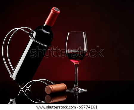 bottle with red wine on a stand and glass - stock photo