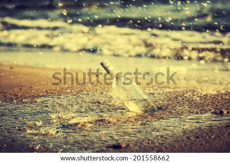 Bottle with water drops on beach, retro instagram vintage effect. - stock photo