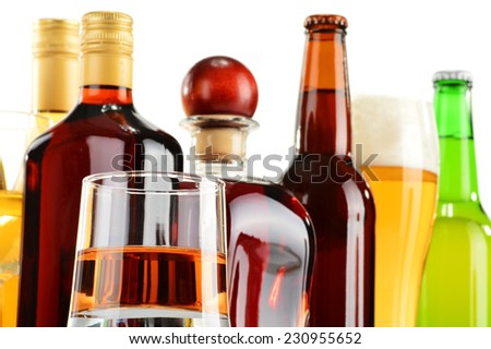 Bottles and glasses of assorted alcoholic beverages over white background - stock photo