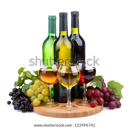 bottles and glasses of wine and assortment of grapes, isolated on white