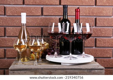 Bottles and glasses of wine and ripe grapes on box on brick wall background - stock photo