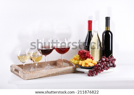 Bottles and glasses of wine and ripe grapes on table in room - stock photo