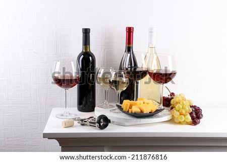 Bottles and glasses of wine, cheese and ripe grapes on table in room - stock photo