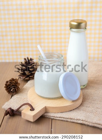 bottles and jars with fresh milk on wooden Coaster