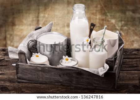 bottles and jars with fresh milk products in old wooden crate with gunny sack on old used background - stock photo