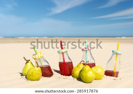 Bottles lemonade and fresh fruit at the beach - stock photo