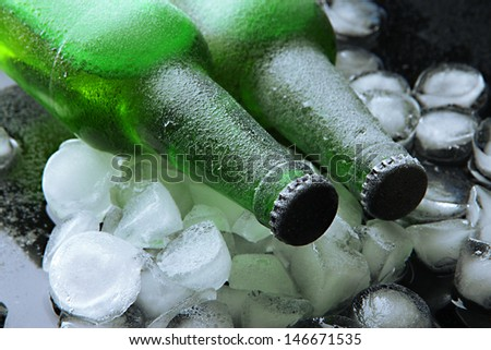 Bottles of beer with ice cubes, close up
