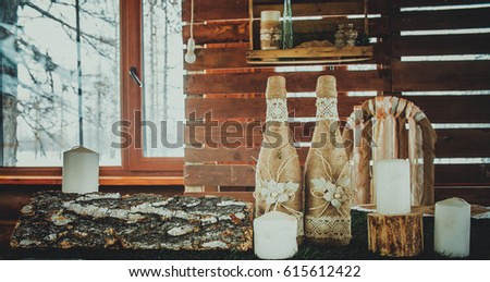 Bottles of champagne and white candles are beautifully packaged and stand on a table on a wooden background