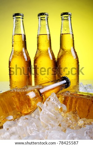 Bottles of cold and fresh beer with ice over yellow background