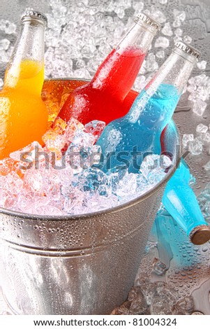 Bottles of cooler drinks with ice on stainless steel counter - stock photo