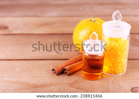 Bottles of essential oil and bath salt with orange and cinnamon on wooden background - stock photo