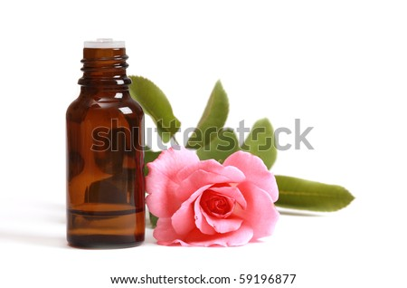 Bottles of essential oil and pink rose - stock photo
