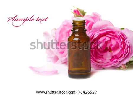 Bottles of essential oil and pink rose isolated over white - stock photo