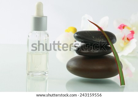 bottles of essential oil and set of stones with yellow flower - stock photo