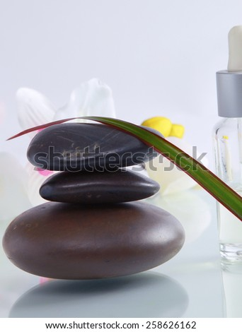 bottles of essential oil and set  stones with flower - stock photo