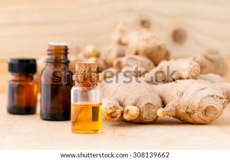 Bottles of ginger oil and ginger on wooden background with selective focus. - stock photo