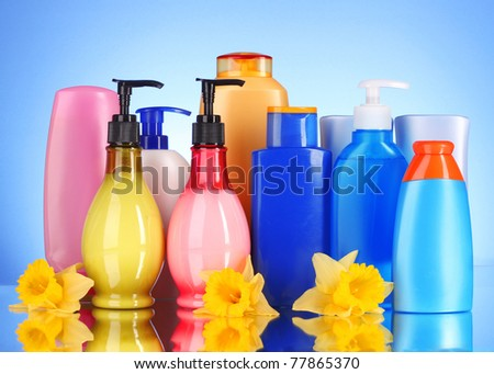 bottles of health and beauty products on blue background with reflection - stock photo
