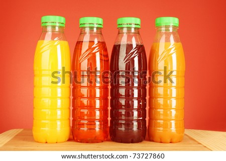 bottles of juice on red  background - stock photo