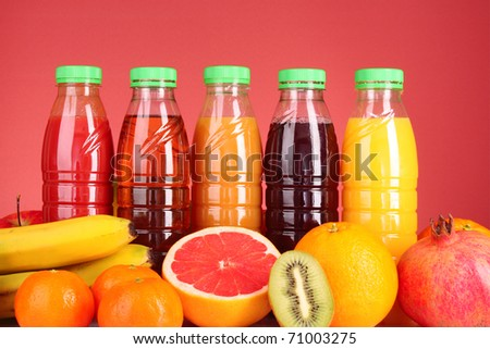bottles of juice  with ripe fruits on red background