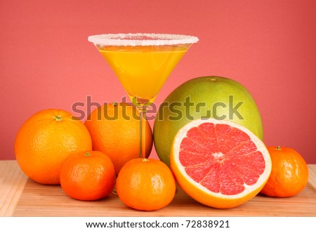 bottles of juice  with ripe fruits on yellow background - stock photo