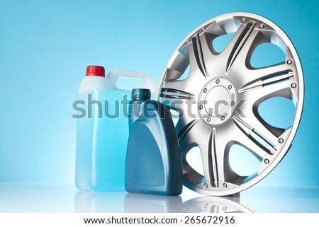 bottles of motor oil and alloy wheel - stock photo