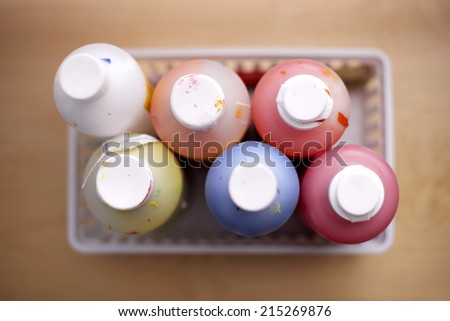 Bottles of multi-coloured paints, close-up, overhead view (still life, differential focus)