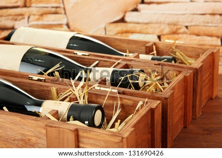 Bottles of old red wine in gift wooden box, on stone background - stock photo
