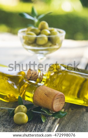 bottles of olive oil and olives on vintage table