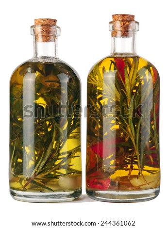 bottles of olive oil with herbs and spices isolated over white background - stock photo
