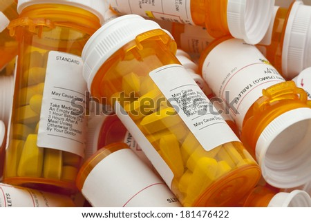 Bottles of prescription medicine in a pile. This collection of pill containers is symbolic of the many medications senior adults and chronically ill people take.  - stock photo