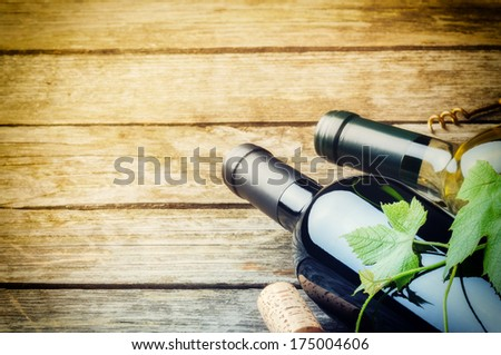 Bottles of red and white wine on wooden background  - stock photo