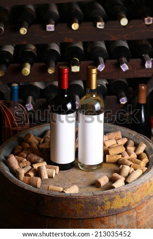 Bottles of red and white wine with blank label templates standing in a wine cellar on a wood barrel