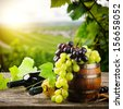 Bottles of red and white wine with fresh grape on vineyard background  - stock photo