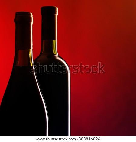 Bottles of red wine on dark red background. Filtered image: vintage effect. - stock photo