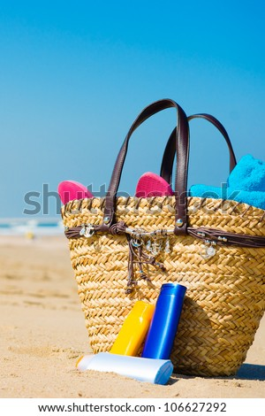 Bottles of sun screen in a basket - stock photo