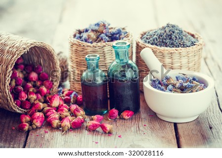 Bottles of tincture, basket with rose buds, lavender and dried forget me not flowers in mortar. Herbal medicine. Selective focus. - stock photo