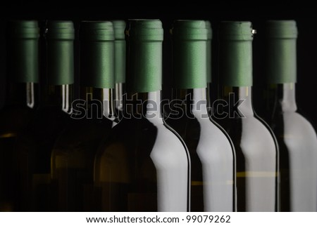 Bottles of white wine in a row with shallow depth of field