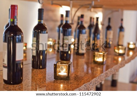 Bottles of wine, candles are on shelf - stock photo