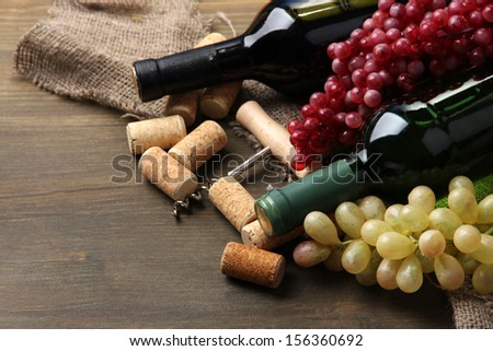Bottles of wine, grapes and corks on wooden background - stock photo