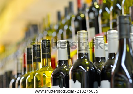 Bottles of wine in rows in liquor store, selective focus. - stock photo