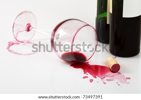 Bottles, overturned glass and wine stains - stock photo