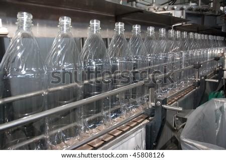 Bottles plastic The Technological line on bottling drink in plastic bottles. Conveyor automatic - stock photo
