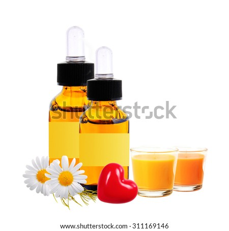 bottles with essence oil, chamomiles and candles isolated on white - stock photo