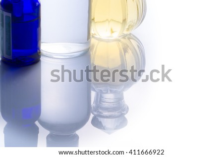 Bottles with essential oils and flower isolated on white background - stock photo
