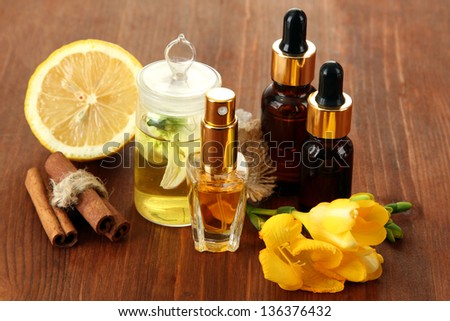 Bottles with ingredients for the perfume on wooden background - stock photo